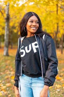 Gelukkig mooi jong meisjesmodel met zwarte stijlvolle casual jas en jeans loopt in een herfstpark met geel herfstgebladerte
