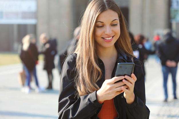 Gelukkig mooi jong middelbare schoolmeisje met slimme telefoon in openlucht op zonnige en de lentedag die texting glimlachen