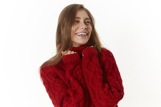 Gelukkig mooi jong wijfje dat een kastanjebruine sweater met lange mouwen draagt, vreugdevol smilijg. positief vriendelijk meisje met charmante brede glimlach, binnenshuis poseren in stijlvolle gebreide trui