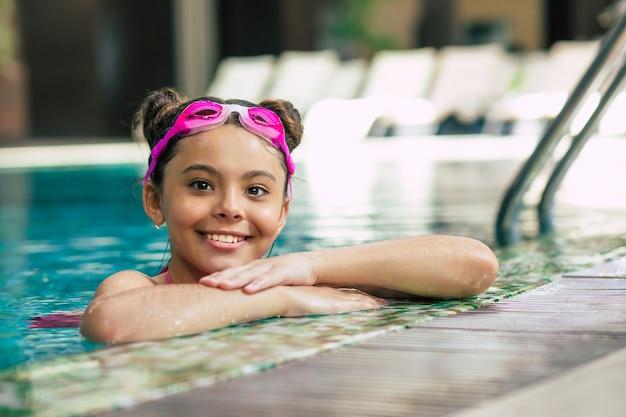 Gelukkig mooi klein glimlachend meisje in bril en zwembroek in het zwembad heeft plezier tijdens vakantie of zwemlessen.