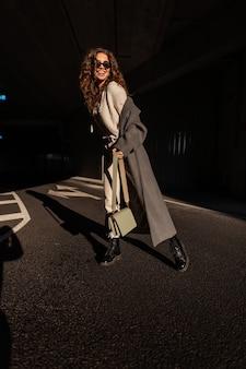Gelukkig mooi krullend meisje met een glimlach met zonnebril in een modieuze lange jas met een stijlvolle handtas in de stad op het zonlicht en de schaduw. grappige vrouw in casual stedelijke stijl buitenshuis