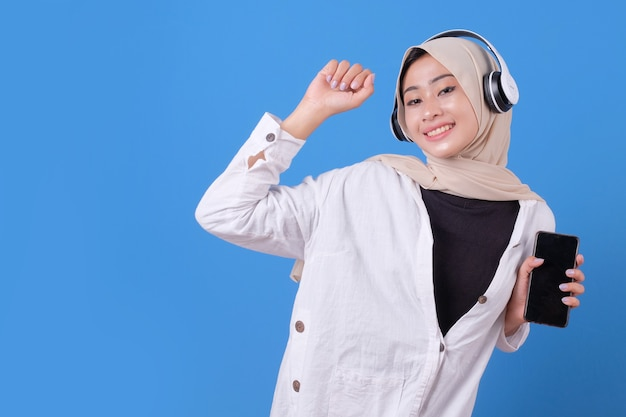 Gelukkig mooi meisje dansen en luisteren muziek in draadloze hoofdtelefoons, smartphone te houden