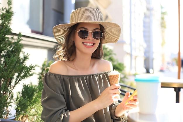 Gelukkig mooi meisje dat een ijsje eet terwijl ze in het zomerstraatcafé zit.