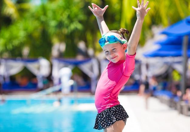 Gelukkig mooi meisje dat pret in openlucht zwembad heeft