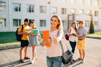 Gelukkig mooi meisje dat zich met notaboeken bevindt en rugzak die duim toont en glimlacht