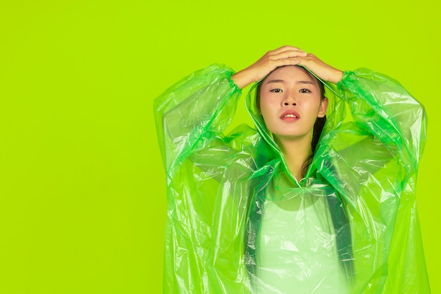 Gelukkig mooi meisje, groene kleding, paraplu en jas, regenachtige dag dragen.