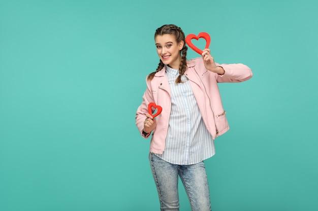 Gelukkig mooi meisje in casual stijl, vlecht haar en roze jas, permanent en rood hart vormen te houden en kijken naar camera met met brede glimlach, indoor, geïsoleerd op blauwe of groene achtergrond