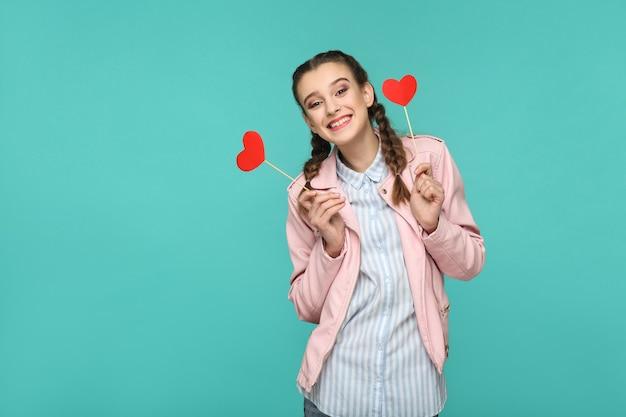 Gelukkig mooi meisje in casual stijl, vlecht kapsel en roze jas, permanent en rood hart stickers te houden en kijken naar camera en toothy glimlachen, indoor, geïsoleerd op blauwe of groene achtergrond