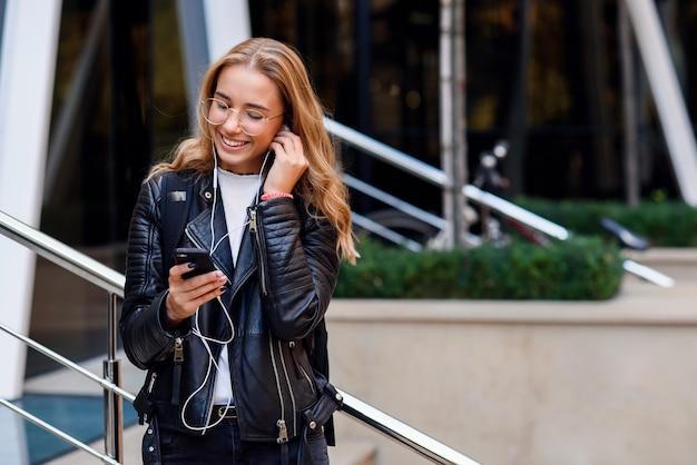 Gelukkig mooi meisje in stedelijke achtergrond luistert naar muziek met een koptelefoon. blij meisje loopt op straat.