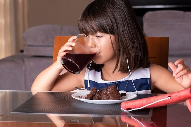 Gelukkig mooi meisje kijken naar tablet en het eten van chocoladetaart