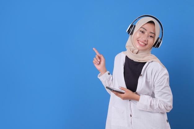Gelukkig mooi meisje luisteren muziek in draadloze hoofdtelefoons, smartphone te houden