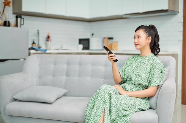 Gelukkig mooi meisje met afstandsbediening tv kijken