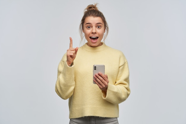 Gelukkig, mooi meisje met blond haar verzameld in een broodje. gele trui dragen en een smartphone vasthouden. vinger opsteken, opgemerkt. heb een idee. kijkend naar de camera, geïsoleerd over witte muur
