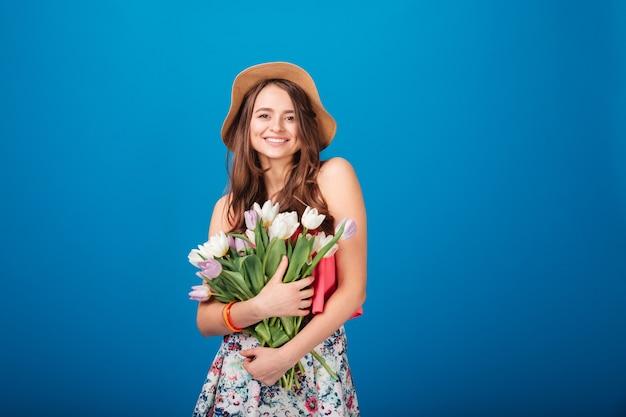 Gelukkig mooi meisje met boeket bloemen over blauwe achtergrond