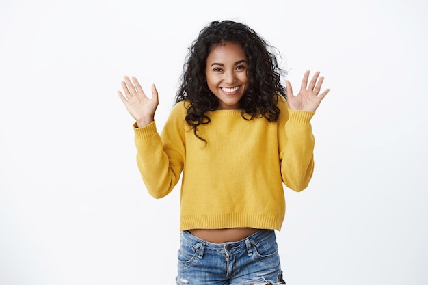Gelukkig mooi meisje met krullend haar dat opwinding en geluk toont, vrienden begroet, met opgeheven handpalmen zwaait hallo, hallo gebaar, kan eindelijk een nieuwe gele trui dragen, koude herfstdag