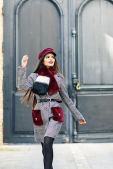 Gelukkig mooi meisje met zeer lang haar die winterjas en glb in openlucht dragen.