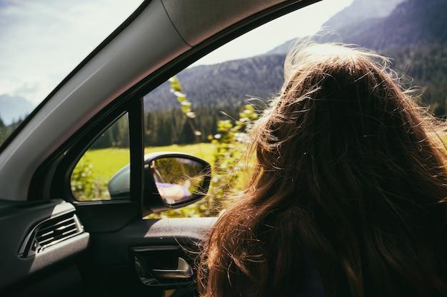 Gelukkig mooi meisje reizen in een auto over de bergen dolomieten, italië. europa