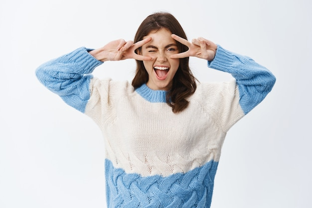 Gelukkig mooi meisje toont vredes-v-teken en glimlacht zorgeloos, drukt positieve en vrolijke emoties uit, staat vrolijk tegen de witte muur