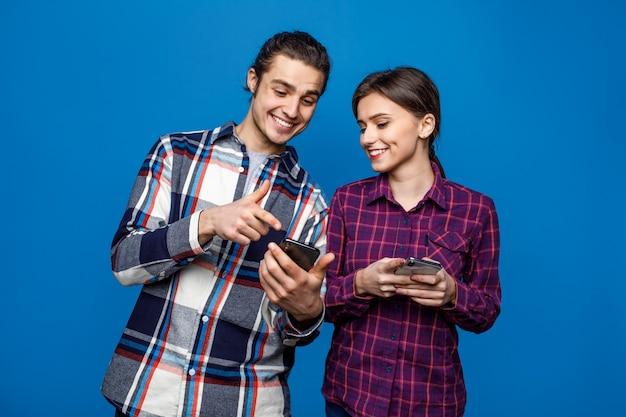 Gelukkig mooi paar dat t-shirts draagt status geïsoleerd over blauw Premium Foto