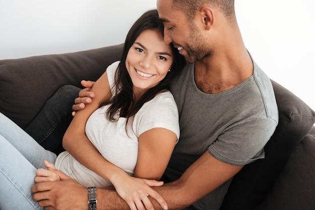 Gelukkig mooi paar lachen op een bank thuis tijdens het knuffelen. vrouw die naar voren kijkt.