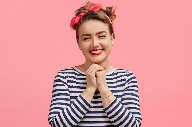 Gelukkig mooi prachtig europees vrouwelijk model in casual gestreepte trui, houdt de handen bij elkaar, blij om complimenten te ontvangen, drukt oprechte positieve emoties uit, modellen alleen binnenshuis.