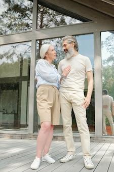 Gelukkig mooi senior paar in zomer outfits kijken elkaar terwijl staande tegen landhuis