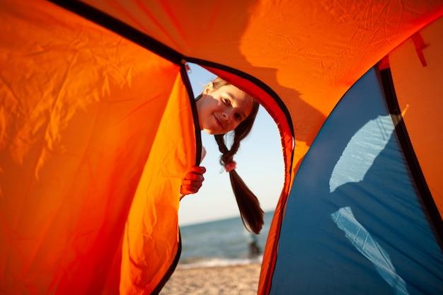 Gelukkig mooi vrolijk jong meisje staat in de buurt van een lichte tent aan de zanderige oever van de blauwe zee en glimlacht kijken naar de camera