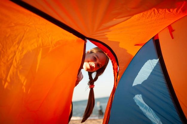Gelukkig mooi vrolijk jong meisje staat in de buurt van een lichte tent aan de zanderige oever van de blauwe zee en glimlacht te kijken naar de camera