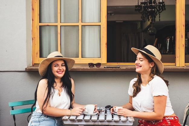 Gelukkig mooi vrolijk paar mensen jonge vrouwen vrienden genieten van koffie en cappuccino aan de vleermuis zitten op een tafel buiten