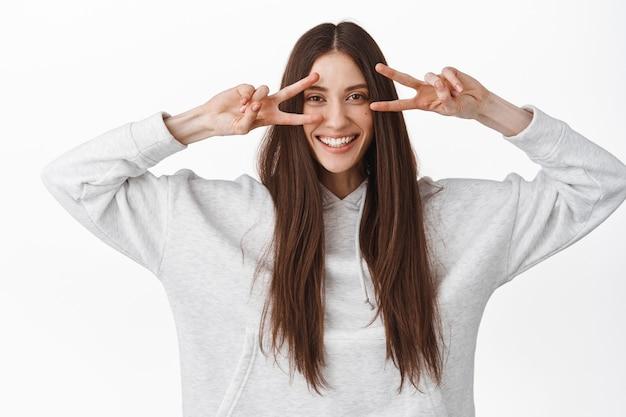 Gelukkig mooi vrouwelijk model met lang gezond steil haar, met v-teken vredesgebaar, disco vingers over ogen, breed glimlachend, staande tegen de witte muur