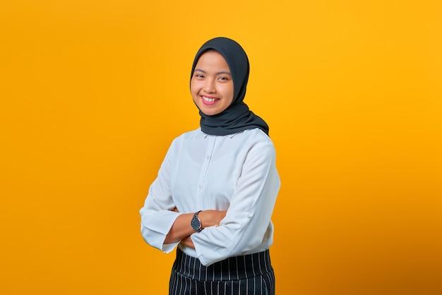 Gelukkig mooie aziatische vrouw permanent met gekruiste arm en camera kijken op gele achtergrond