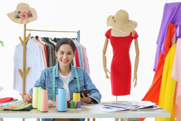 Gelukkig mooie aziatische vrouwelijke modeontwerper zitten en glimlachen. ze gebruikt tabletcomputer voor contact met haar online consument.