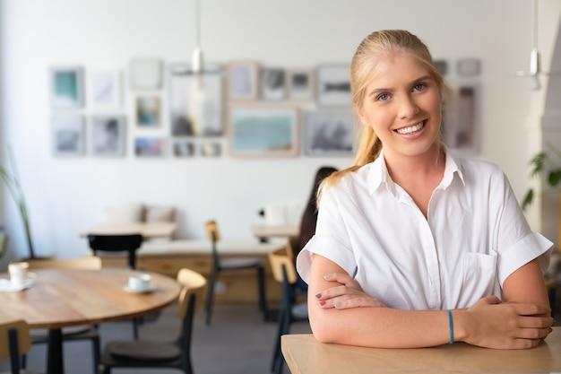 Gelukkig mooie blonde vrouw draagt een wit overhemd, permanent in co-werkruimte, leunend op bureau, poseren,