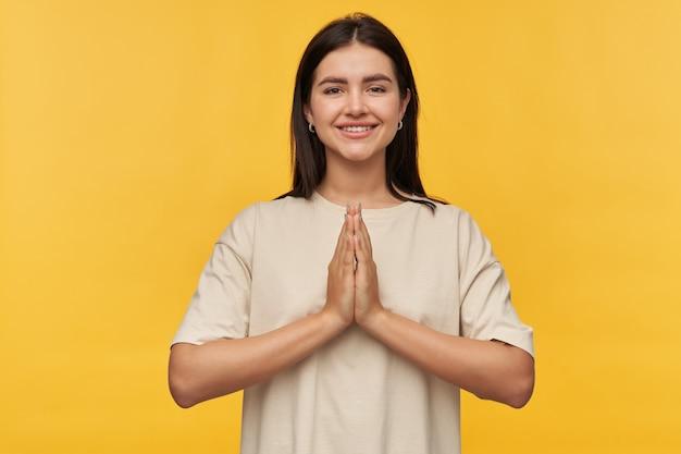 Gelukkig mooie brunette jonge vrouw in witte t-shirt houdt handen in biddende positie over gele muur