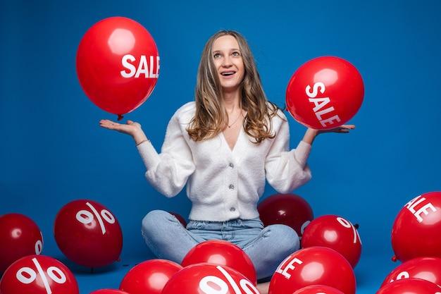 Gelukkig mooie dame die op haar handpalmen twee rode ballonnen met de inscriptie verkoop, geïsoleerd op blauwe muur