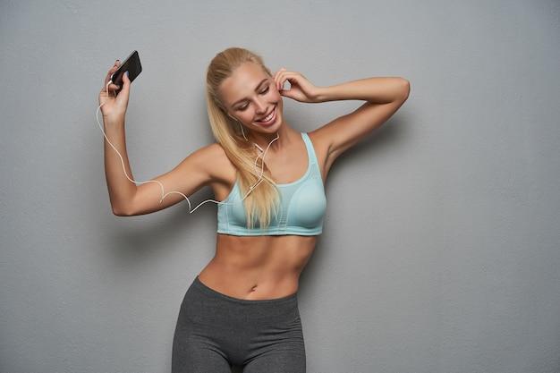 Gelukkig mooie gezonde blonde vrouw met casual kapsel dragen van dansen op muziek op haar koptelefoon, ogen gesloten houden en genieten van favoriete nummer, geïsoleerd over grijze achtergrond