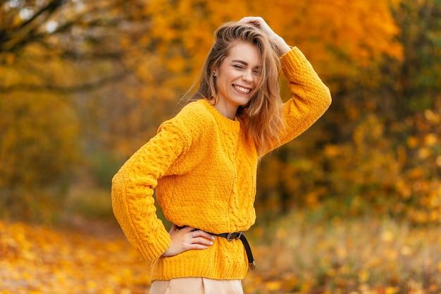 Gelukkig mooie glimlachende vrouw in vintage gele gebreide trui loopt in het park met oranje herfstbladeren buitenshuis