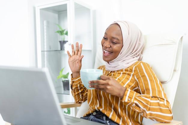 Gelukkig mooie islamitische afrikaanse vrouw met behulp van laptop zittend op een gezellige bank. mooie jonge moslimvrouw gebruikt een laptop en glimlacht terwijl ze thuis op de bank zit