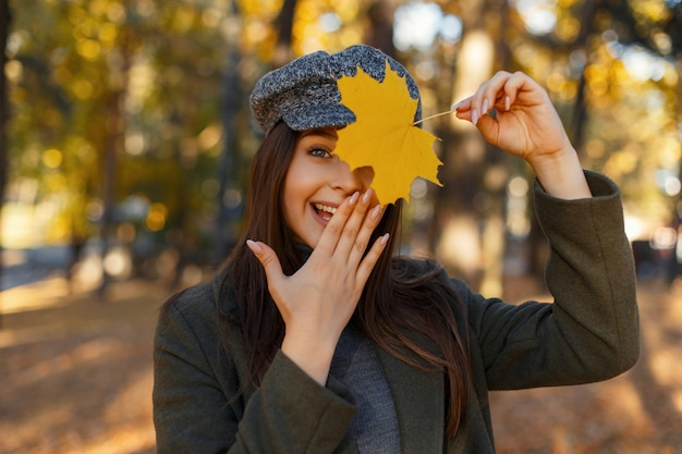 Gelukkig mooie jonge aantrekkelijke vrouw met een glimlach in een modieuze jas en hoed bedekt haar gezicht met haar hand en een geel herfstblad in het park. emotie van vreugde en verwondering