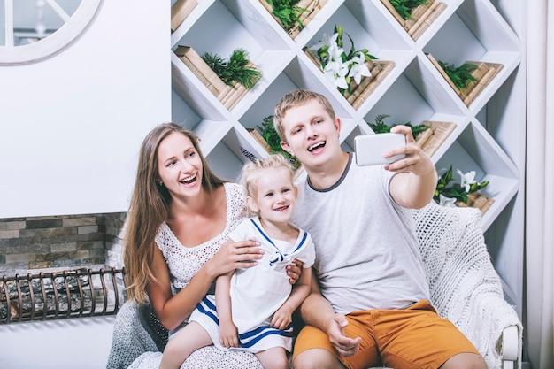 Gelukkig mooie jonge familie vader, moeder en dochter doen selfie op mobiele glimlach samen thuis