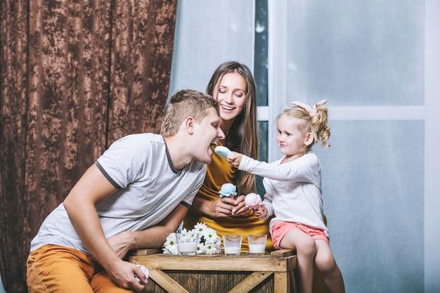 Gelukkig mooie jonge familie vader, moeder en dochter drinken melk en spelen samen in het huis van de picknick