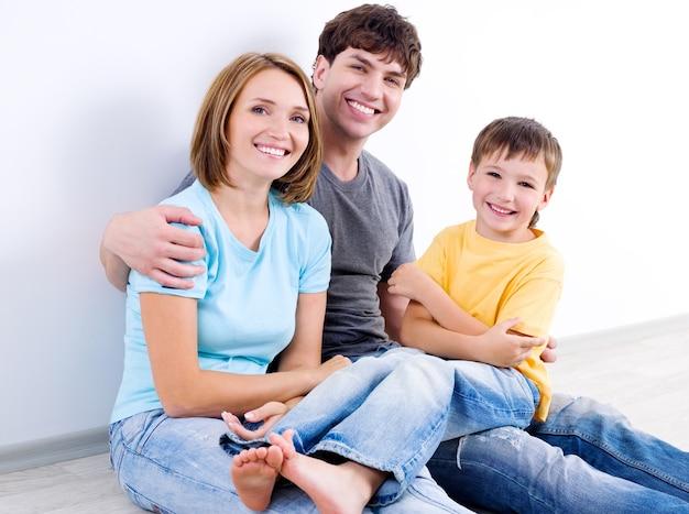 Gelukkig mooie jonge gezin in casuals zittend op de vloer - binnenshuis