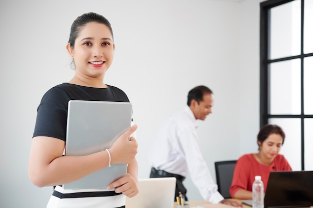 Gelukkig mooie jonge indiase vrouwelijke ondernemer permanent in moderne kantoor met laptop in handen en glimlachen