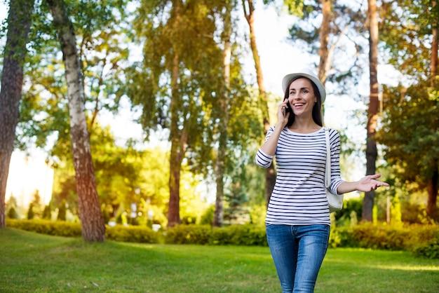 Gelukkig mooie jonge student vrouw in een hoed met slimme telefoon en rugzak terwijl ze buiten in het park loopt