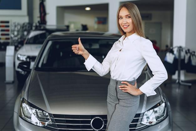 Gelukkig mooie jonge vrouw autodealer in showroom