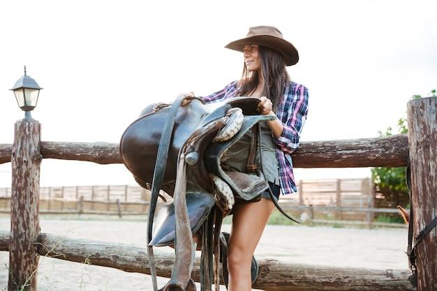 Gelukkig mooie jonge vrouw cowgirl in hoed staande en zadel vast te houden voor het berijden van paard