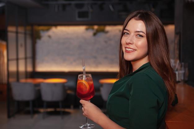 Gelukkig mooie jonge vrouw die lacht naar de camera terwijl het hebben van een drankje aan de bar