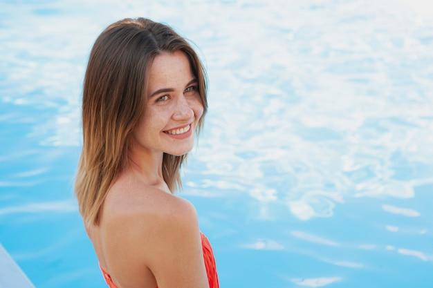 Gelukkig mooie jonge vrouw die lacht, wegkijken, ontspannen aan het zwembad. vrolijke vrouw die van warme zonnige dag genieten dichtbij het zwembad