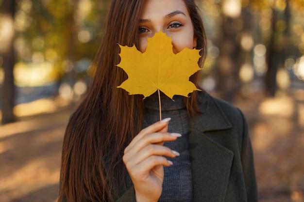Gelukkig mooie jonge vrouw glimlacht en heeft betrekking op haar gezicht met gele herfst esdoornblad in het park