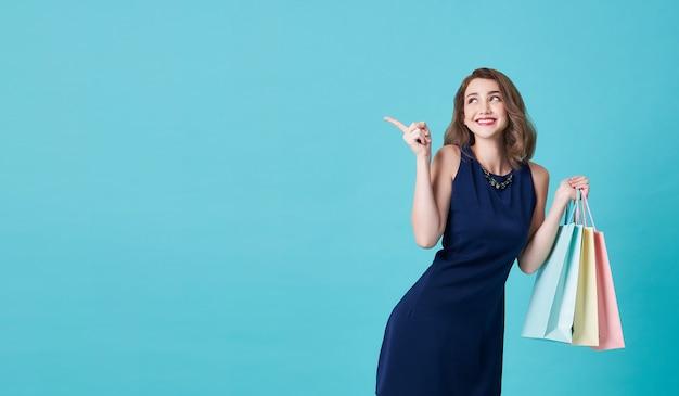 Gelukkig mooie jonge vrouw in blauwe jurk met zijn hand met boodschappentassen en vinger wijzend op op lichtblauw met kopie ruimte.